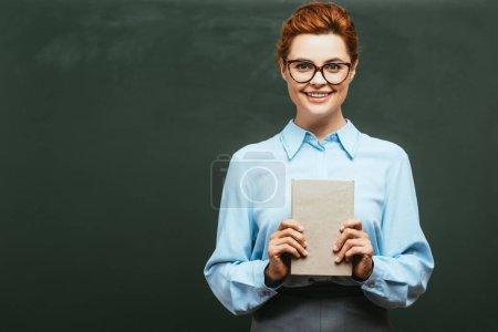 Photo pour Professeur heureux dans les lunettes tenant le livre tout en se tenant près du tableau - image libre de droit