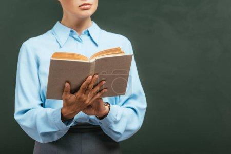 Photo pour Vue recadrée du livre de lecture de l'enseignant tout en se tenant près du tableau - image libre de droit