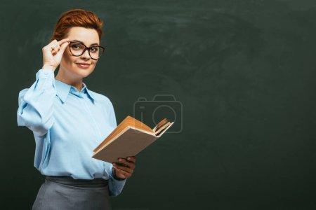 Photo pour Professeur souriant touchant lunettes tout en se tenant près du tableau avec livre ouvert - image libre de droit