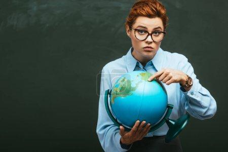 Foto de Hermoso joven profesor señalando con el dedo en el globo mientras está de pie cerca de pizarra - Imagen libre de derechos