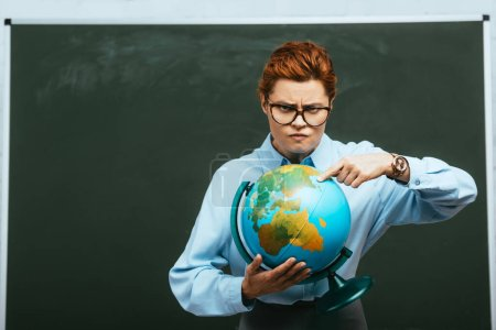 strict teacher pointing with finger at globe while standing near chalkboard