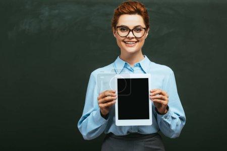 Photo pour Professeur joyeux montrant tablette numérique avec écran vide tout en se tenant près du tableau - image libre de droit