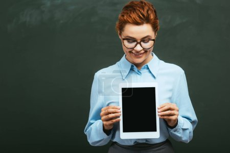 smiling teacher holding digital tablet with blank screen while standing near chalkboard