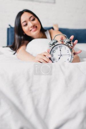 Photo pour Foyer sélectif de sourire asiatique femme tenant réveil sur le lit le matin - image libre de droit