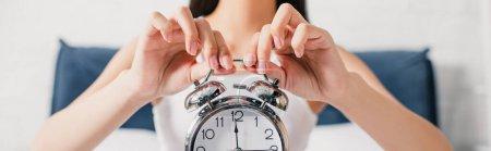 Photo pour Recadrage horizontal de la jeune femme tenant réveil dans la chambre - image libre de droit