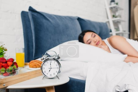Selective focus of alarm clock and breakfast on bedside table and asian woman sleeping on bed