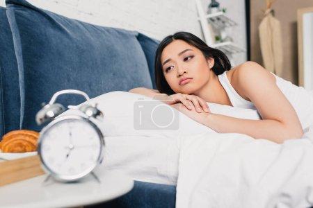foyer sélectif de triste asiatique fille couché sur le lit près réveil et petit déjeuner sur table de chevet