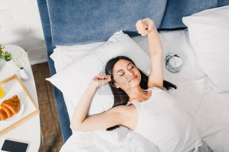 Top view of asian girl stretching near alarm clock, smartphone and breakfast on bedside tale