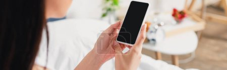 Photo for Horizontal crop of woman holding smartphone with blank screen on bed - Royalty Free Image