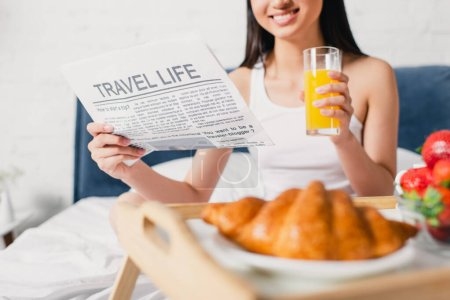 Cropped view of smiling woman holding newspaper with travel life lettering and glass of orange juice on bed at morning