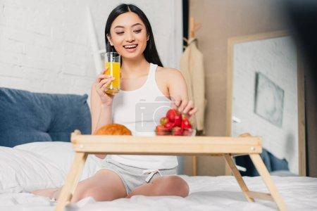 Photo pour Foyer sélectif de gai asiatique fille tenant verre de jus d'orange près du petit déjeuner avec des fraises sur le lit - image libre de droit