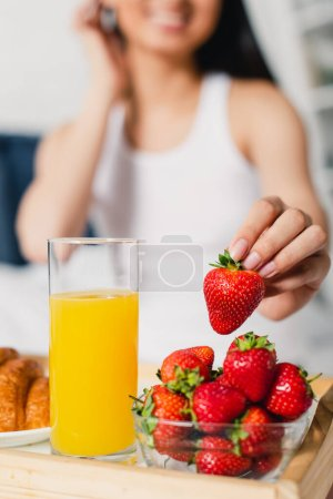 Photo for Selective focus of woman taking fresh strawberry near glass of orange juice and croissant on breakfast tray - Royalty Free Image