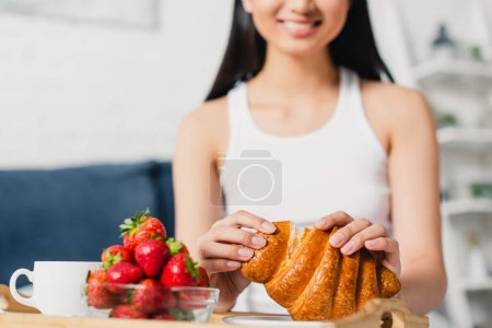 Selective focus of smiling woman holding croissant near strawberries and coffee in bedroom