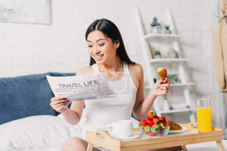 Selective focus of cheerful asian girl reading news near breakfast with fresh strawberries and croissant on bed