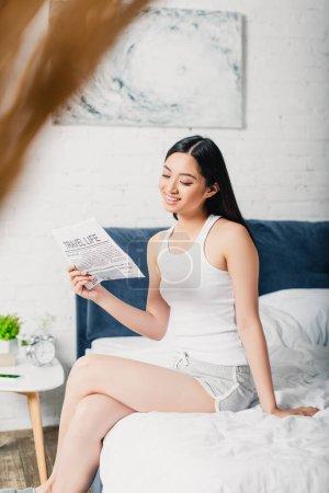 Photo pour Foyer sélectif de sourire asiatique femme lecture journal tandis que assis sur lit - image libre de droit