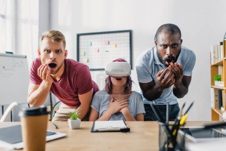 Selective focus of shocked multiethnic business people with vr headset in office