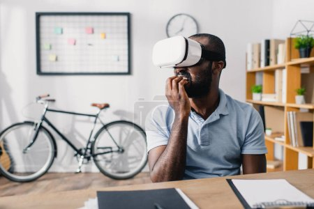 Selective focus of scared african american businessman using vr headset in office