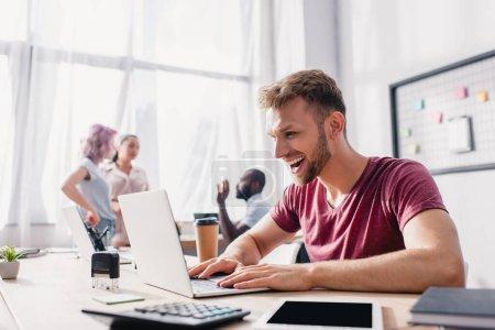 Foto de Enfoque selectivo del hombre de negocios que usa el ordenador portátil en la mesa mientras sus colegas hablan en segundo plano en la oficina - Imagen libre de derechos