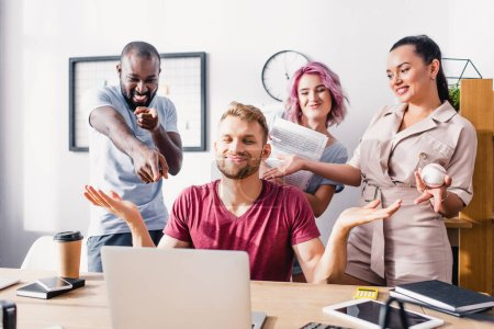 Photo for Selective focus of multiethnic business people pointing at colleague showing shrug gesture in office - Royalty Free Image