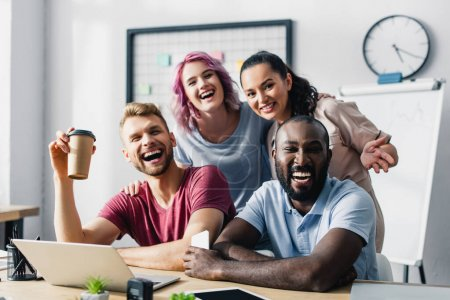 Selective focus of multiethnic business people looking at camera while working together in office