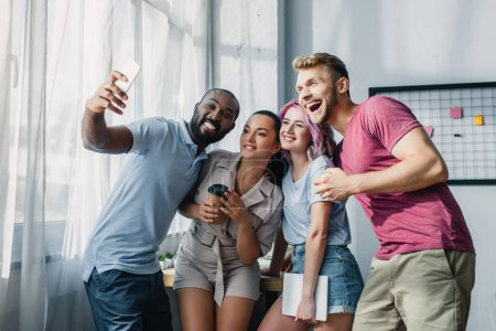 Photo for Young multiethnic business people with coffee to go and gadgets taking selfie in office - Royalty Free Image