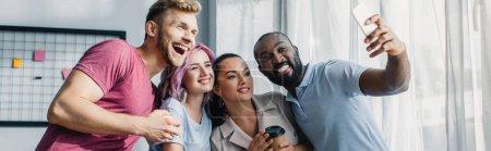 Photo pour Image horizontale de gens d'affaires multiethniques prenant selfie avec smartphone au bureau - image libre de droit
