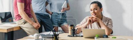Panoramakonzept einer Geschäftsfrau, die den Stift in der Hand hält und in die Kamera schaut, während sie am Tisch in der Nähe von Kollegen im Büro arbeitet