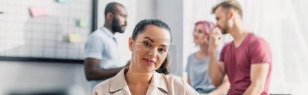 Photo pour Image horizontale d'une femme d'affaires regardant une caméra avec des collègues multiculturels en arrière-plan au bureau - image libre de droit