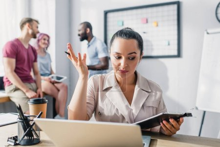 Selective focus of businesswoman holding clipboard and pen while working at table in office