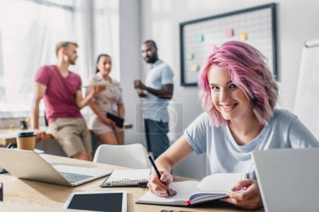 Selective focus of businesswoman writing on notebook near gadgets on table in office