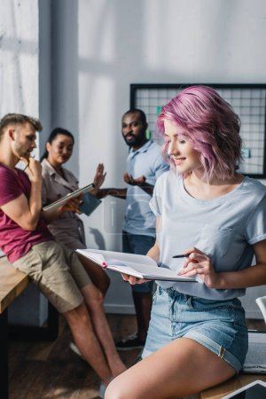 Enfoque selectivo de la empresaria sosteniendo pluma y cuaderno con compañeros de trabajo multiétnicos en el fondo en la oficina