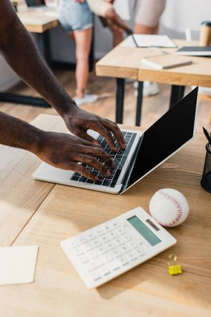Cropped view of african american businessman using laptop with blank screen near calculator and baseball ball on office table