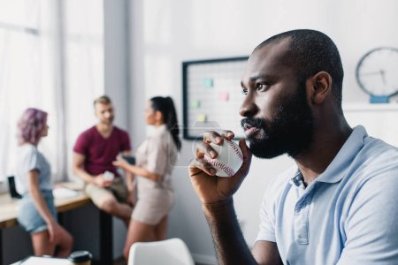 Photo pour Concentration sélective de coûteux homme d'affaires afro-américain tenant une balle de baseball au bureau - image libre de droit