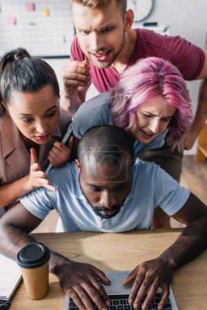 Photo pour Des gens d'affaires multiculturels concentrés regardant un collègue afro-américain utilisant un ordinateur portable à la table au bureau - image libre de droit