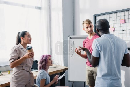Photo for Selective focus of business people looking at african american colleague while working near whiteboard in office - Royalty Free Image