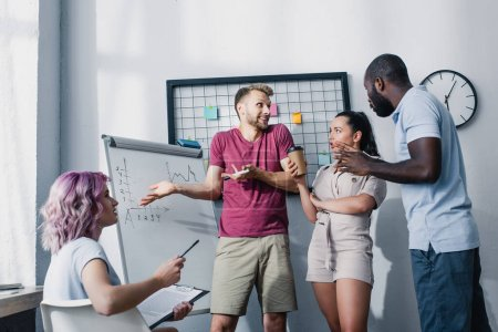 Photo for Multicultural business people working near whiteboard in office - Royalty Free Image