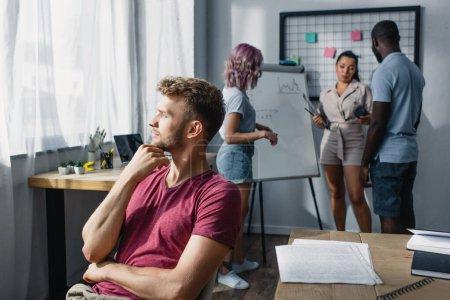 Selektiver Fokus nachdenklicher Geschäftsleute, die neben Zeitungen auf dem Tisch sitzen, während multikulturelle Kollegen im Hintergrund arbeiten