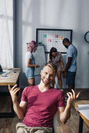 Photo pour Concentration sélective de jeunes hommes d'affaires regardant la caméra avec des collègues multiethniques en arrière-plan dans le bureau - image libre de droit