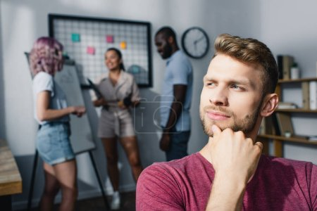 Selective focus of pensive businessman looking away while multiethnic colleagues working in office
