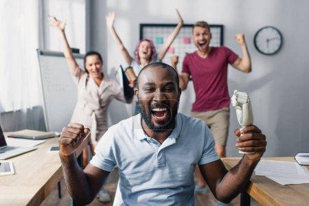 Photo pour Concentration sélective de l'homme d'affaires afro-américain montrant un geste ouais avec des collègues en arrière-plan - image libre de droit