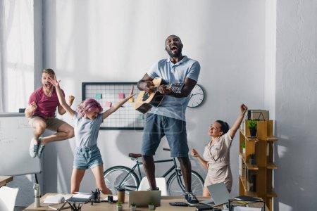 Foto de Enfoque selectivo del empresario afroamericano tocando la guitarra acústica mientras colegas multiétnicos bailan en la oficina - Imagen libre de derechos