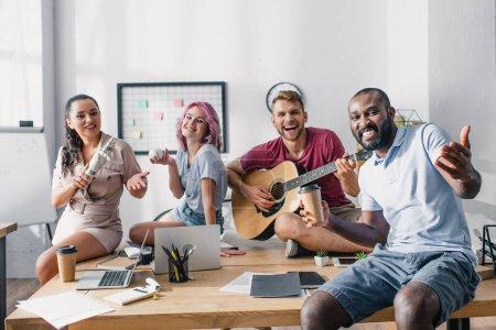Photo pour Jeunes hommes d'affaires multiethniques avec balle de baseball, café à emporter et guitare acoustique regardant la caméra au bureau - image libre de droit