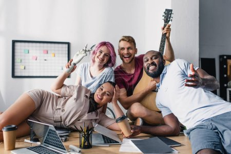 Multiethnic business people with acoustic guitar sitting near laptops and papers on table in office