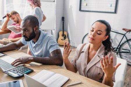 Enfoque selectivo de la mujer de negocios sosteniendo pluma cerca de colega afroamericano y gadgets en la mesa en la oficina