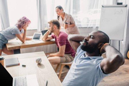 Foto de Enfoque selectivo del hombre de negocios afroamericano con las manos cerca de la cabeza sentado en la mesa mientras colegas multiculturales trabajan en la oficina - Imagen libre de derechos