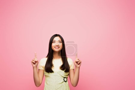 happy asian girl pointing with fingers and looking up isolated on pink