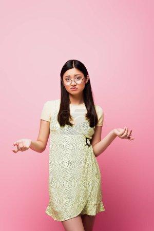 displeased asian girl in glasses showing shrug gesture on pink