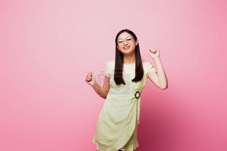 Photo pour Gai et jeune asiatique femme dans lunettes rire sur rose - image libre de droit