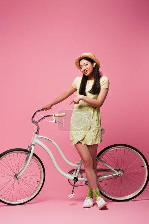 Photo pour Joyeuse asiatique jeune femme en paille chapeau debout près de vélo sur rose - image libre de droit