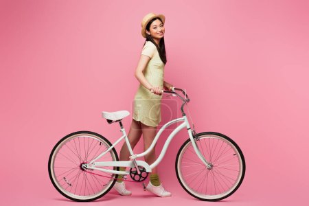 Photo for Cheerful asian young woman in straw hat walking with bicycle on pink - Royalty Free Image